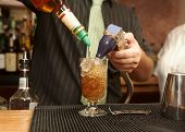 foto of mixing faucet  - Bartender pouring mixed drink of rum and cola - JPG