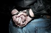stock photo of cuff  - A man is arrested and handcuffed before being transported to jail - JPG