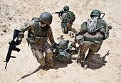 stock photo of medevac  - Squad of soldiers evacuate the injured fellow in arms in the desert - JPG
