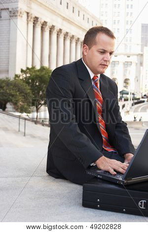 Confident businessman with briefcase using laptop outdoors