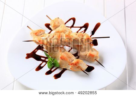 chicken skewers with sauce, on a plate