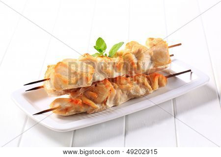 grilled poultry skewers decorated with herb
