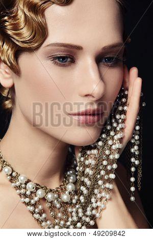 Retrato de mujer joven hermosa con peinado retro y elegante collar