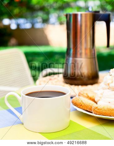 Coffee cup with cookies and moka pot outdoors