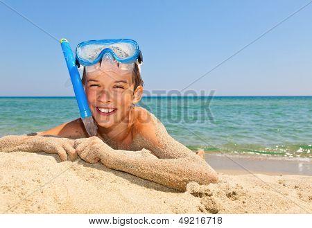 Happy boy wearing snorkeling gear relaxing on the beach