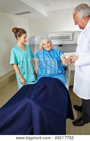 Doctor and nurse with senior patient at MRI machine in radiology