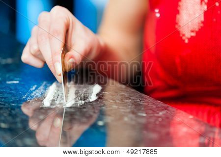 Young woman snorting cocaine with her credit card, close-up