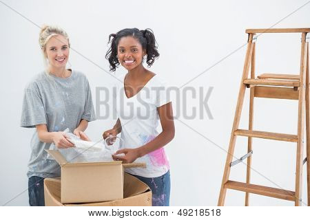 Happy housemates unpacking moving boxes and smiling at camera in new home