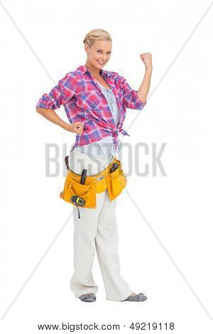 Happy blonde woman tensing arms wearing tool belt on white background