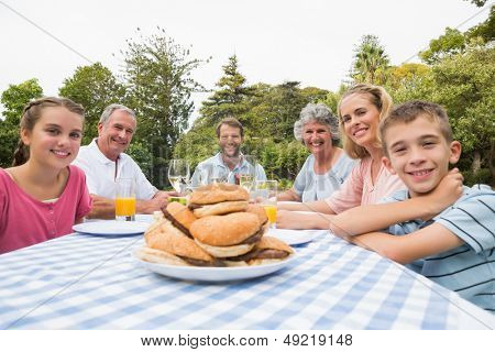 Extended family eating outdoors at picnic table smiling at camera
