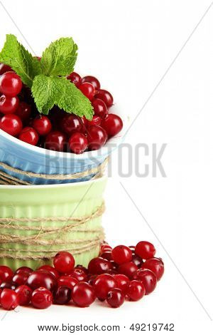 Ripe red cranberries in bowls, isolated on white