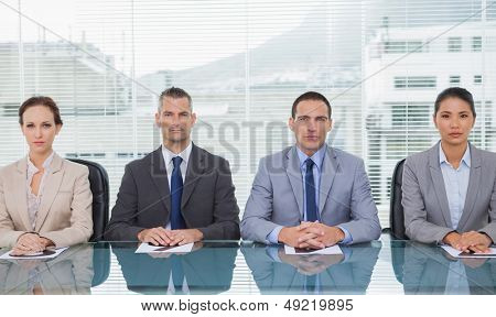 Stern business people sitting straight looking at camera in bright office