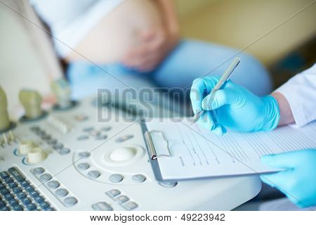 Gloved hand of obstetrician making notes during regular examination at hospital
