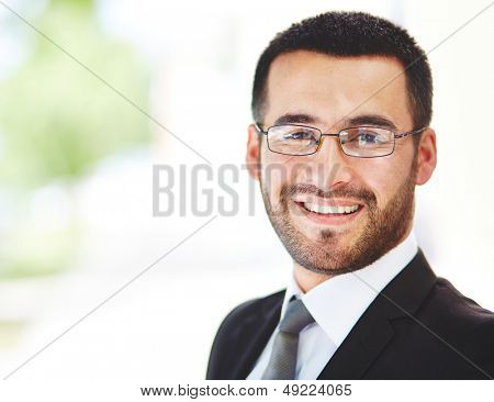 Close-up portrait of a successful businessman looking at camera with smile