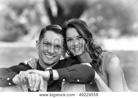 Black And White Version Of A Happy Young Couple Posing Seated On The Ground In A Garden Setting