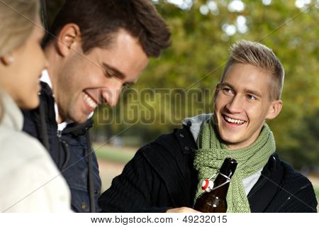 Young companionship smiling outdoors, talking, drinking at autumn.