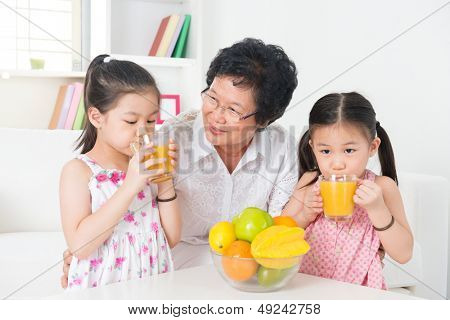 Asian family drinking orange juice. Happy Asian grandparent and grandchildren enjoying cup of fresh squeeze fruit juice at home.