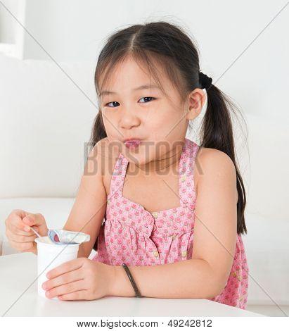 Consumir yogur. Chico asiático feliz comiendo yogur en casa. Niña hermosa. Concepto de salud.
