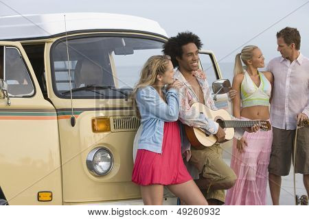 Group of multiethnic young people with campervan