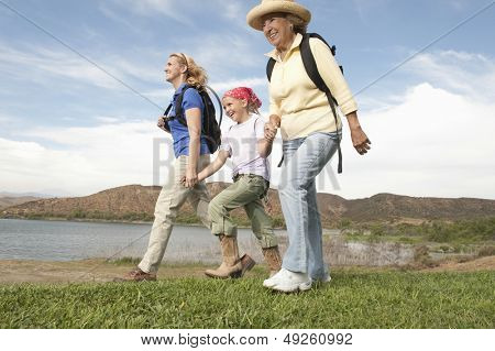Low angle view of happy mother daughter and grand daughter walking by the lake