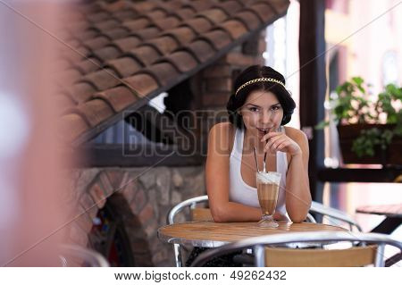 Smiling Girl Drinking Cappuccino In A Cafe