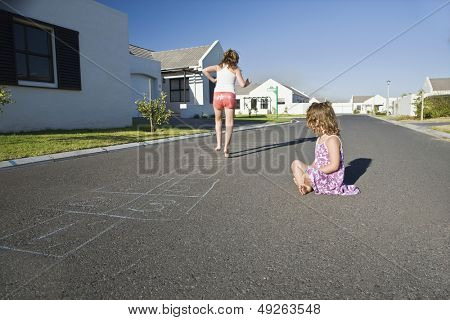 Two young girls playing hopscotch on the street along houses