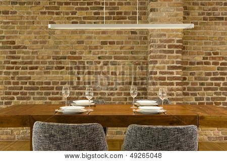 View of wineglasses and plates on dining table against brick wall in modern house