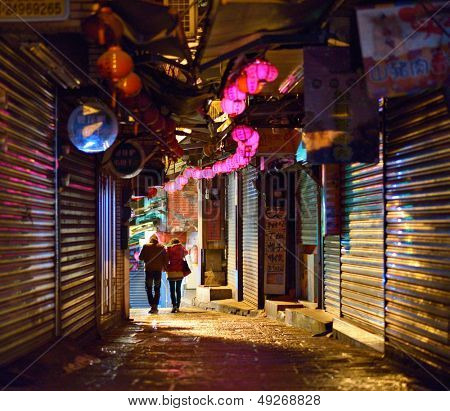 JIUFEN, TAIWAN - JANUARY 17: A couple pass through a shoplined alleyway after hours January 17, 2013 in Jiufen, TW.  The former gold mining city now attracts visitors for its nostalgic scenery.