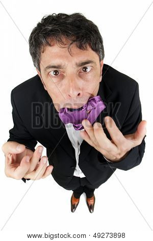 Elegant businessman eating his tie in frustration