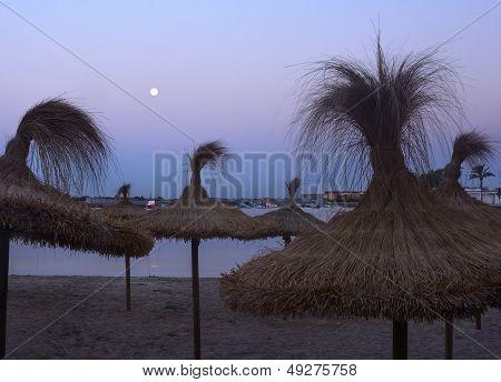 Straw Parasols And Full Moon