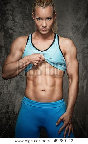 Attractive bodybuilder girl showing her abdominal muscles