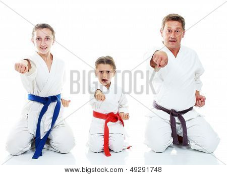 Dad and his daughters sitting in a ritual pose karate and beat his fist on a white background