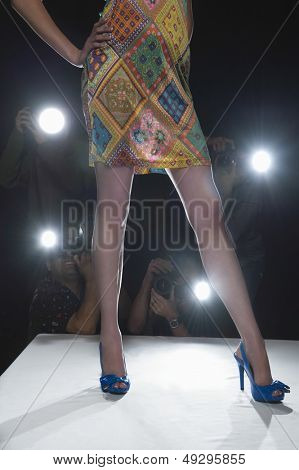 Camera flashing with model in blue high heeled shoes in foreground