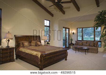 Sleigh bed and sofa in spacious and modern bedroom at home