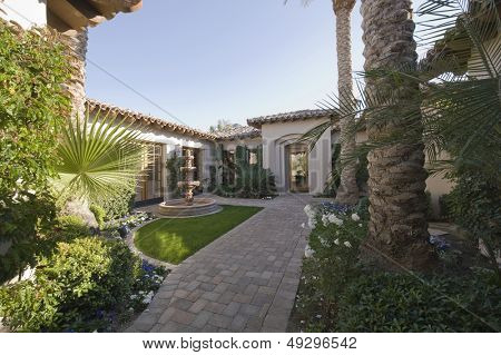 Paved path and plants in garden exterior against house