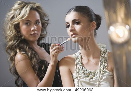 Closeup of a makeup artist applying foundation to fashion model