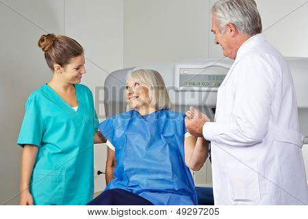 Doctor and MTA helping senior woman in radiology at bone density measurement