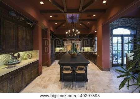 Darkwood and beamed ceiling in modern and spacious kitchen at home