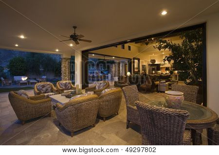 Wicker furniture in lit spacious home with porch view at night