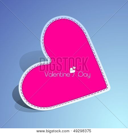 Pink paper heart on blue background for Valentines Day.