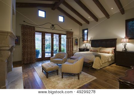 View of a spacious bedroom with seating area and beamed ceiling at home