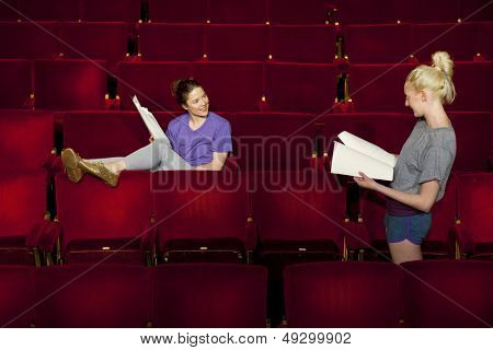 Two young women sitting in theatre stall with scripts