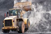 stock photo of slag  - Front loader dumping mineral material on heap - JPG