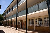 stock photo of school building  - three story deserted elementary school building in sunlight - JPG