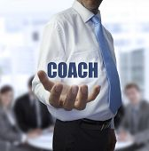 Smart businessman holding the word coach in front of a business team