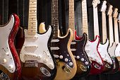 stock photo of string instrument  - Many electric guitars hanging on wall in the music instrument shop - JPG