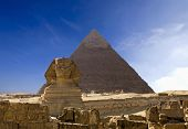 stock photo of pyramid shape  - The famous ancient Egypt Cheops pyramid and sphinx in Giza - JPG