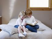 stock photo of storytime  - Full length of two young sisters reading book on a single bed - JPG