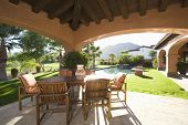 stock photo of hacienda  - Sitting area with sunlit lawn against mountain - JPG
