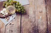 stock photo of vines  - A glass of white wine grapes cashew nuts and soft cheese on a wooden board rustic style background - JPG
